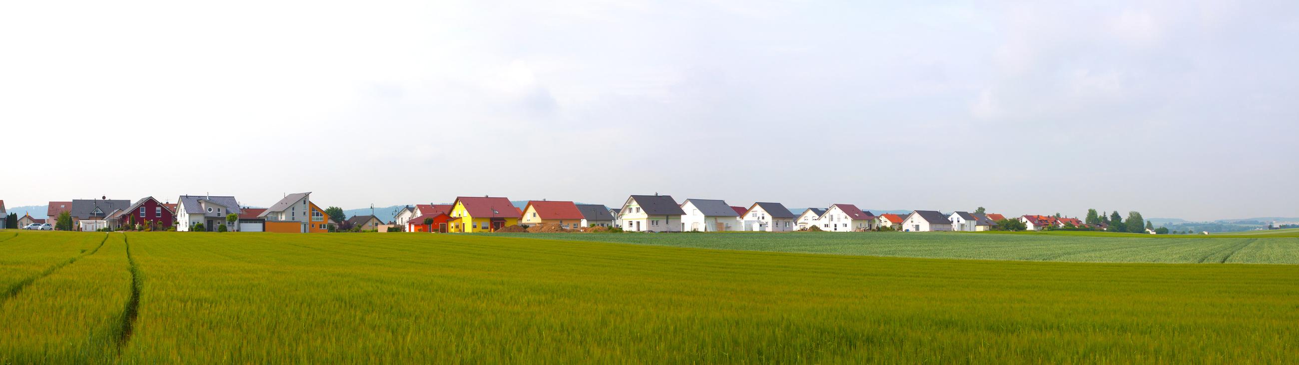 Ackerfläche im Vordergrund, Neubaugebiet im Hintergrund